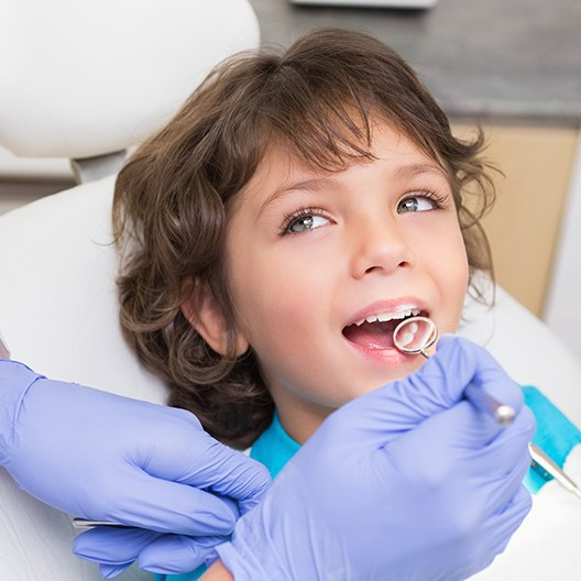 Pediatric dentist examining young patient's smile