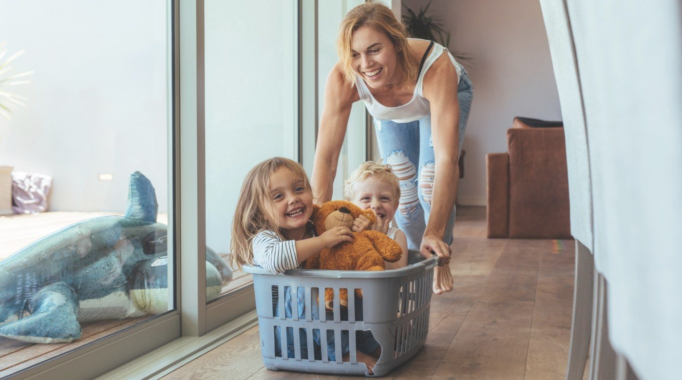 Mother pushing smiling kids in a laundry basket before emergency dentistry