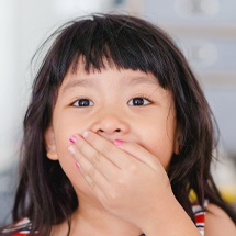 Child with lost filling covering her mouth