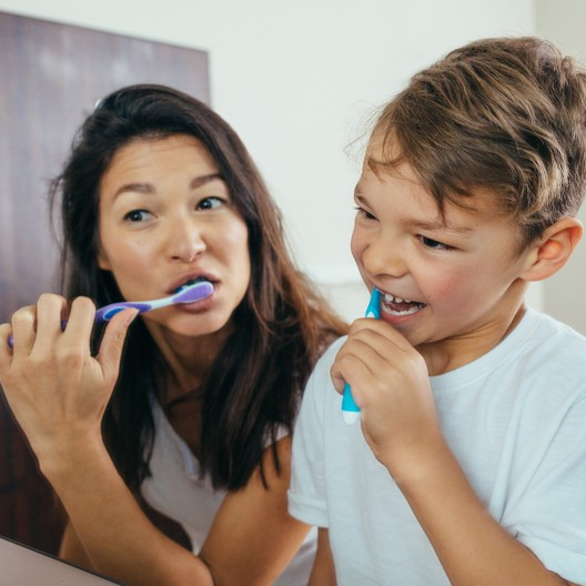 Mother and child brushing teeth together