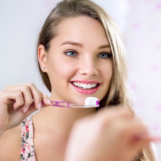 Young woman brushing teeth at home