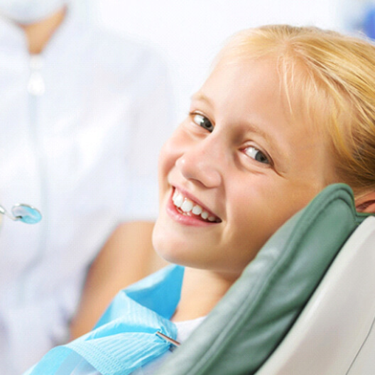 A young girl smiling while seated in the dentist's chair preparing to see a kid's emergency dentist in Palm Harbor