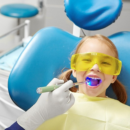Child smiling during dental sealant treatment