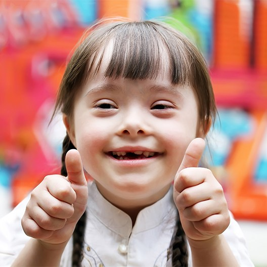 Little girl smiling giving two thumbs up after special needs dentistry visit