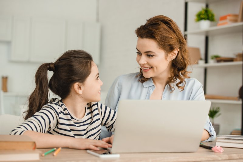 a mother and daughter smiling while seated at the table on a laptop