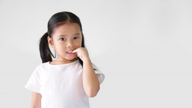 Young girl biting her fingernail